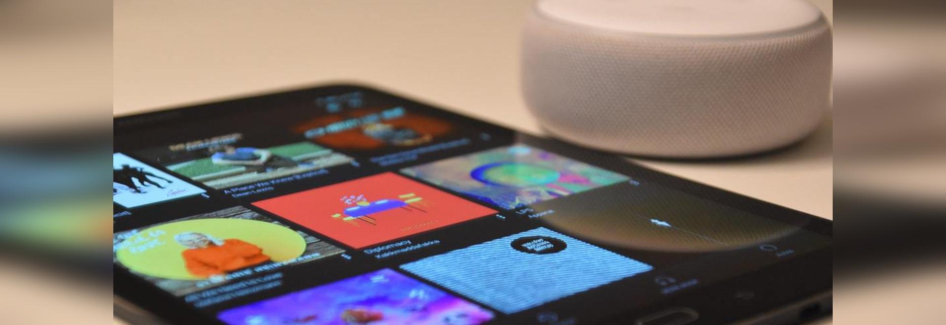 Black tablet computer beside round white portable 'Alexa' speaker