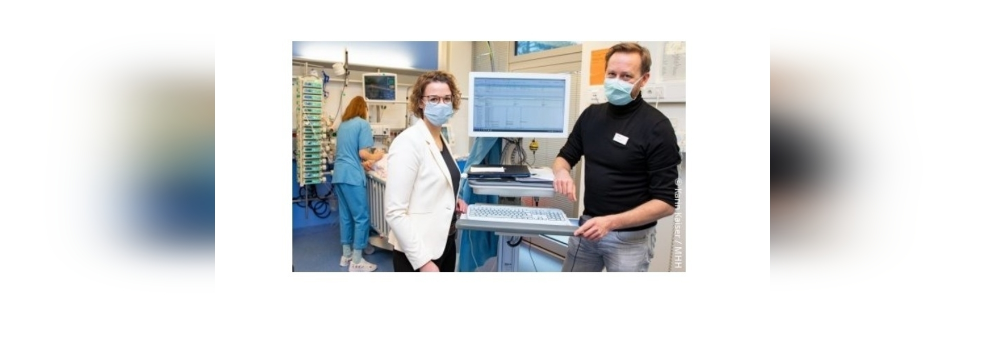 Dr Thomas Jack and Dr Antje Wulff next to a PDMS monitor in the paediatric intensive care unit.