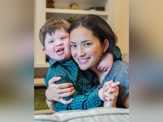 Joshua Copen, who is deaf and has Down syndrome, with his mother, Iara Peng. Copen received cochlear implants to help him hear and learn to speak.
