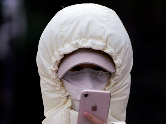 A woman wearing a mask checks her mobile phone in Shanghai, China January 29, 2020.