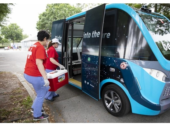Healthcare workers load a container of COVID-19 tests onto a Beep autonomous shuttle bus in March 2020. The self-driving bus then delivered the tests without an onboard attendant to a processing la...